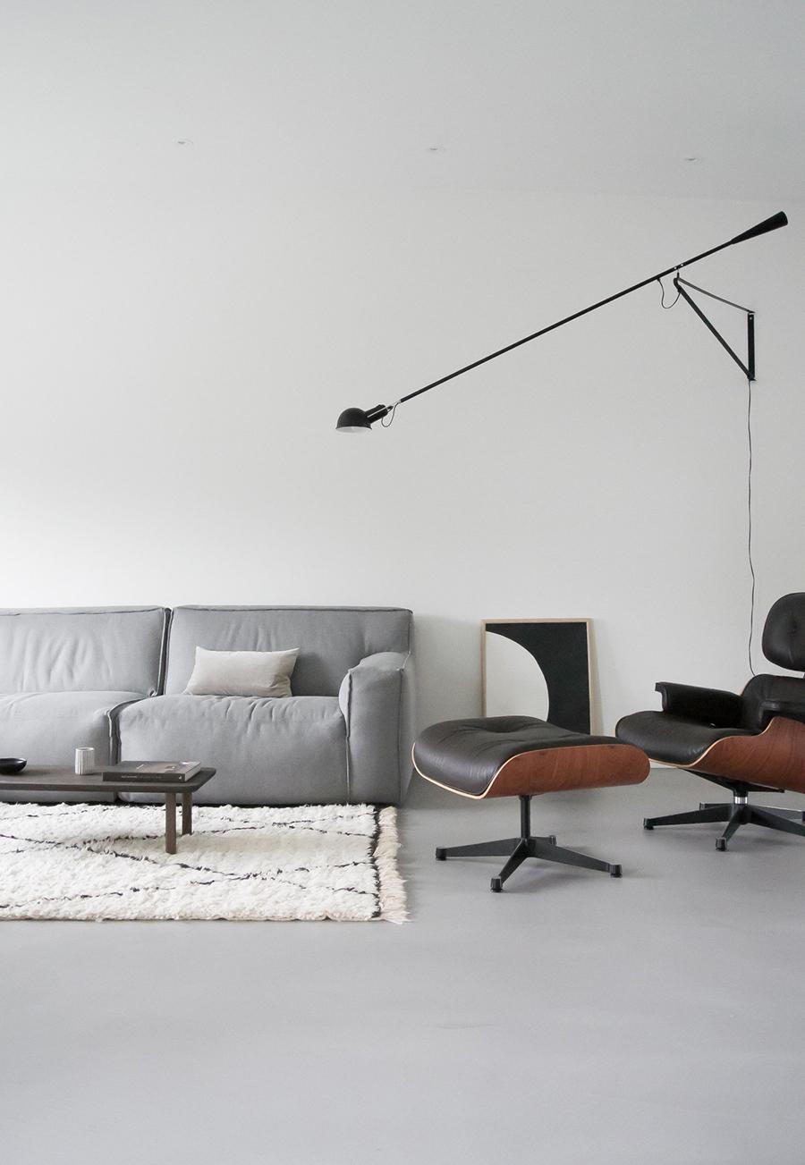Un living muy espacioso con un sofá gris claro, una alfombra, mesa de centro y una poltrona de aspecto ejecutivo urbano. En la pared hay una gran lámpara negra.