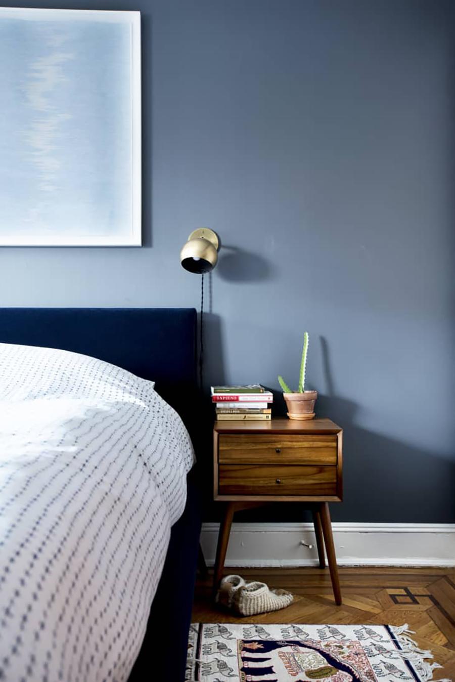 El dormitorio está decorado con una paleta de color monocromática, en este caso de azules. La pared, el respaldo de la cama y el cuadro tienen distintos tonos de azul.