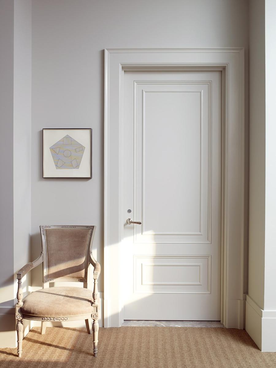 Una puerta blanca con adornos de molduras
