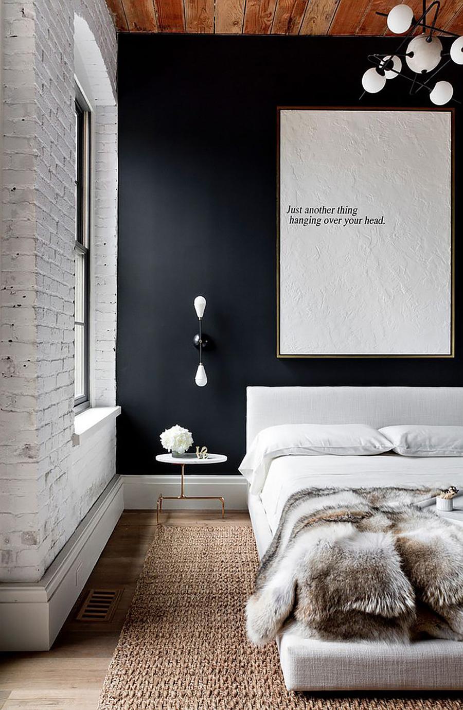 Un dormitorio con una pared blanca de ladrillo expuesto y otra negra, con una cama, alfombra, velador, una pequeña lámpara, una lámpara colgante y un gran cuadro blanco con una frase.