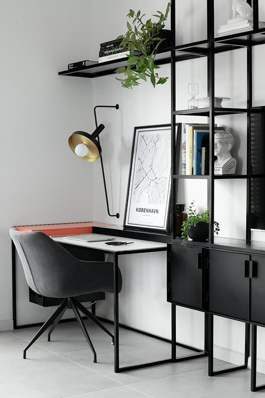 Escritorio en el que predominan los colores blanco y negro. Muebles de metal negro como escritorio y estanterías, una lámpara del mismo color, una silla gris oscura y un cuadro blanco y negro.