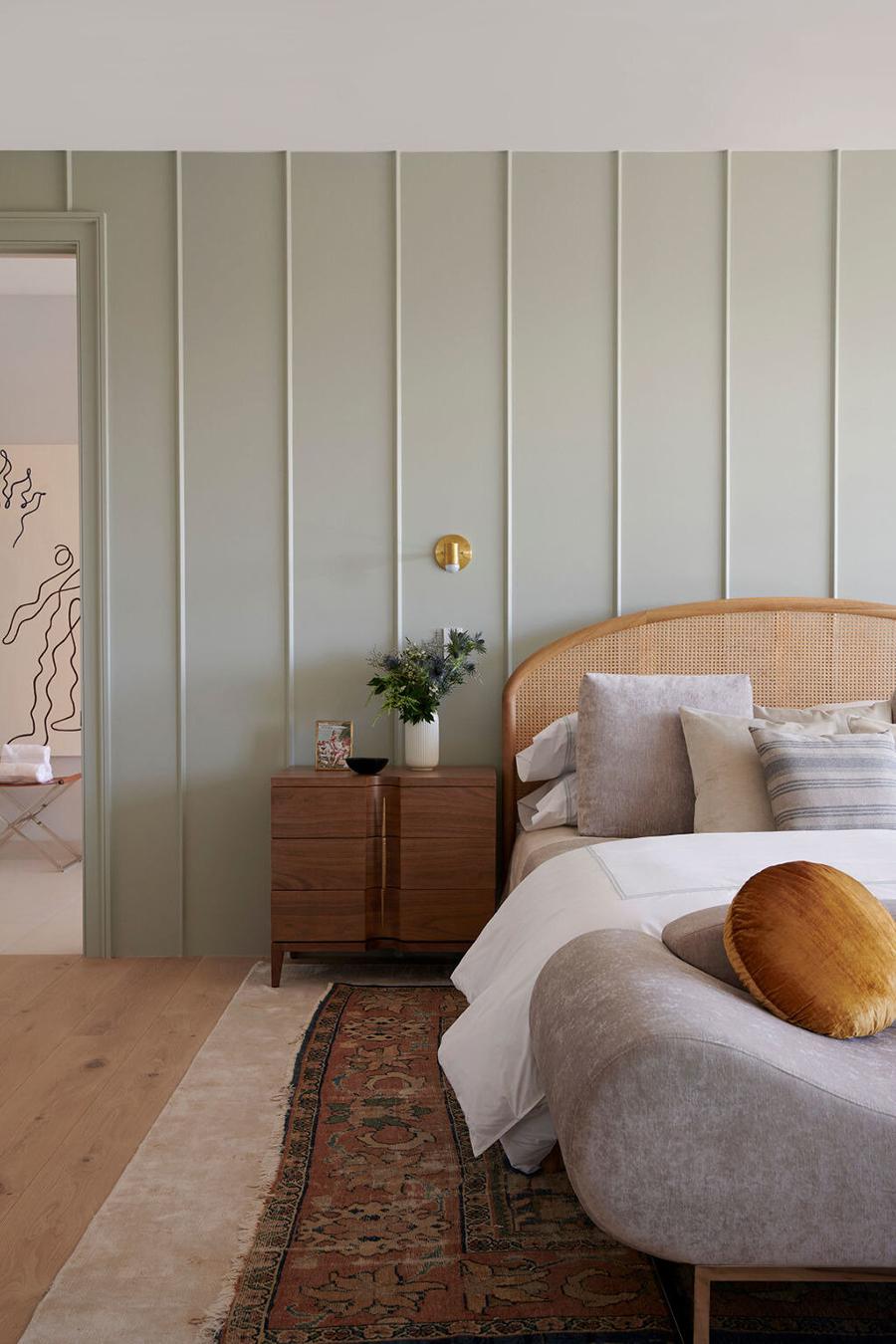 Una pared color verde musgo claro, con molduras en líneas verticales.