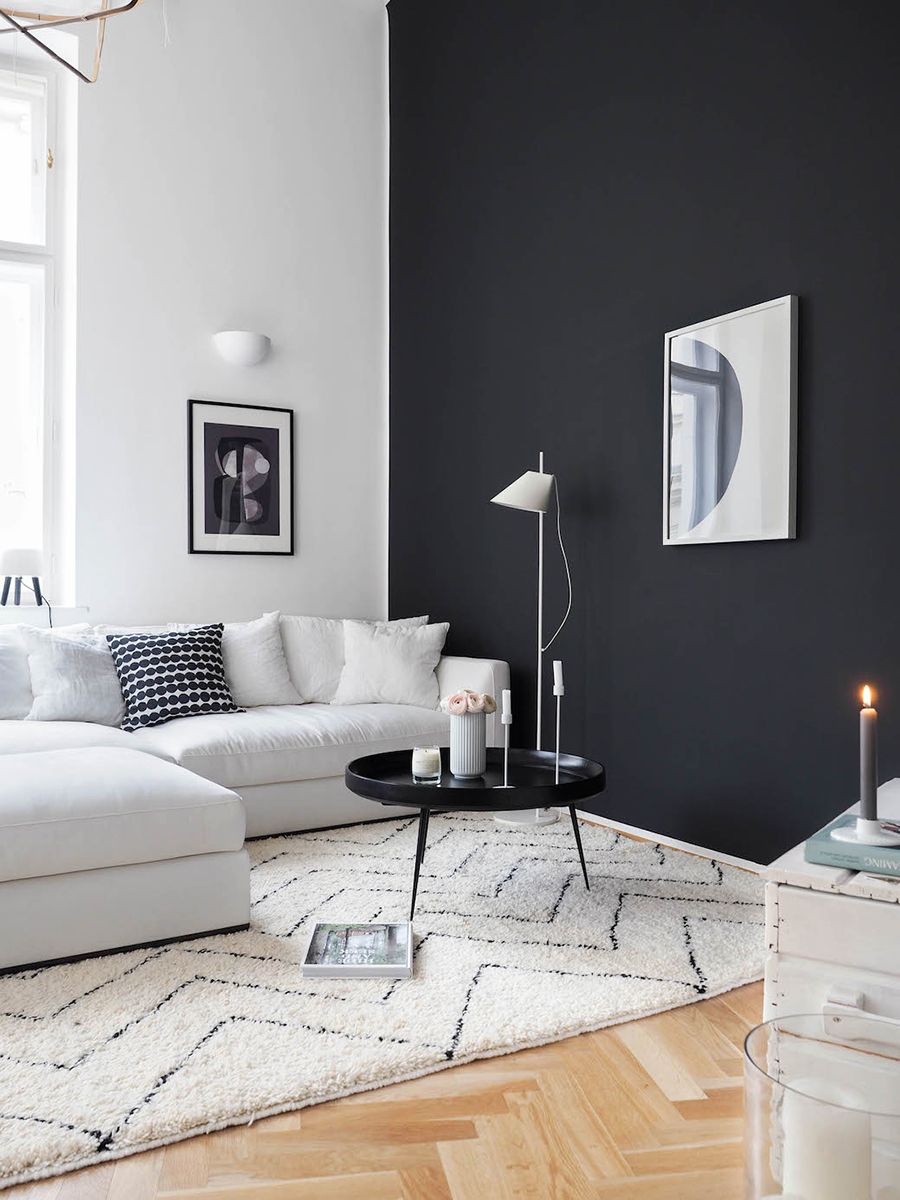 Un living con varios elementos blanco y negro. Un gran sofá blanco con cojines del mismo color excepto uno con motivo blanco y negro. Una mesa de centro negra metálica, cuadros y lámparas.
