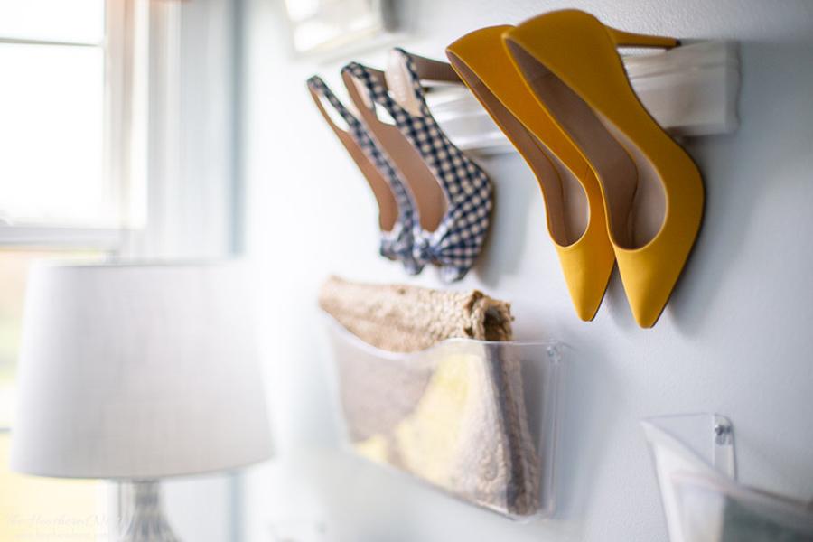Dos zapatos con taco colgados de una repisa, para organización de dormitorio.