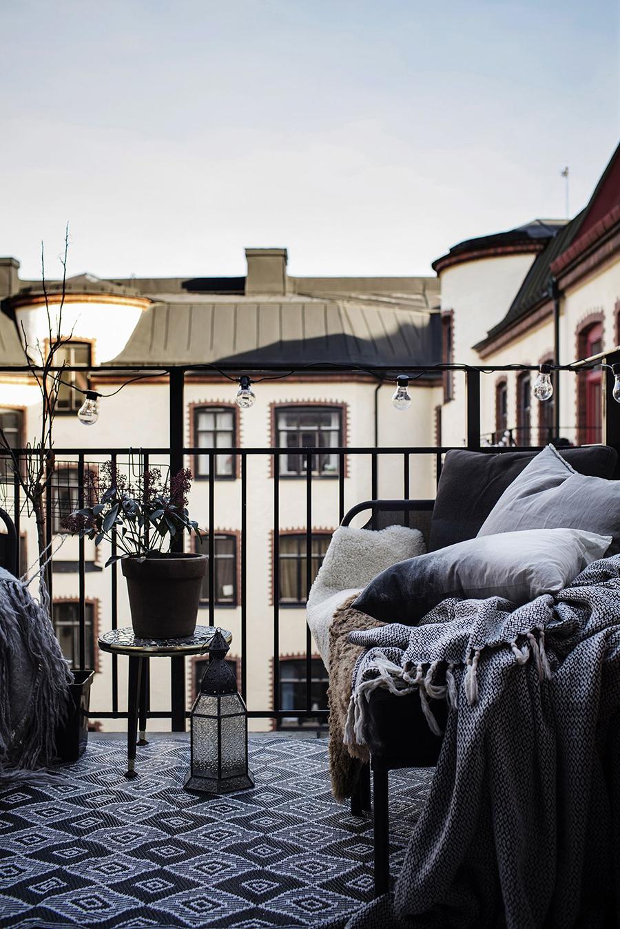 Balcón con muebles de fierro negros. Una mesita con una planta y un sofá con textiles.