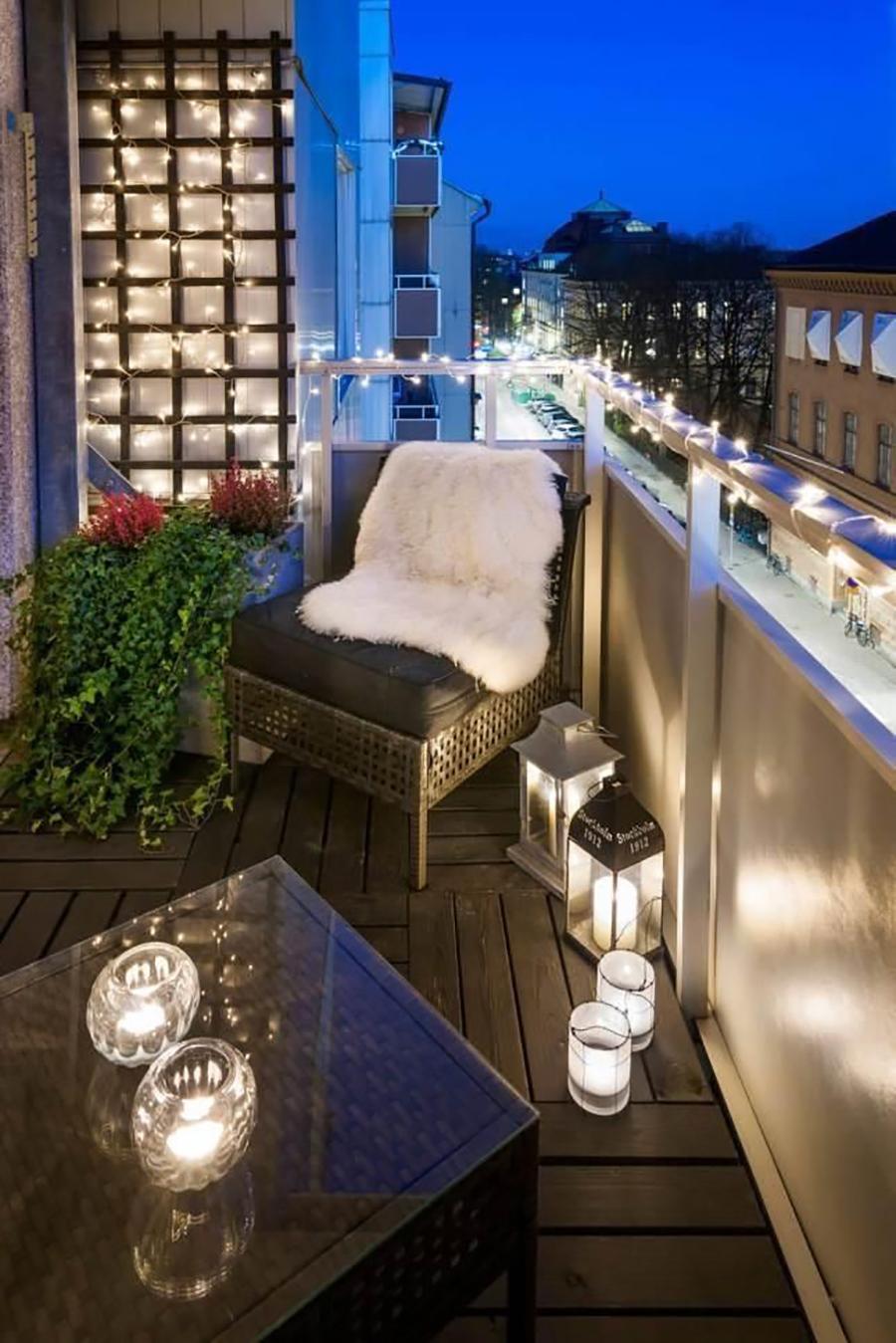 Un balcón con tiras de luces led y fanales. Completan la iluminación velas sobre la mesa y en el piso.