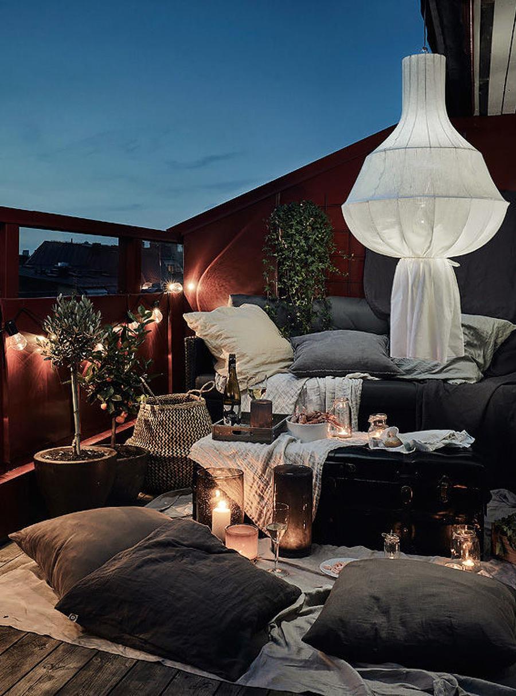 Una terraza con iluminación tenue, creada con la combinación de varias lámparas y velas.