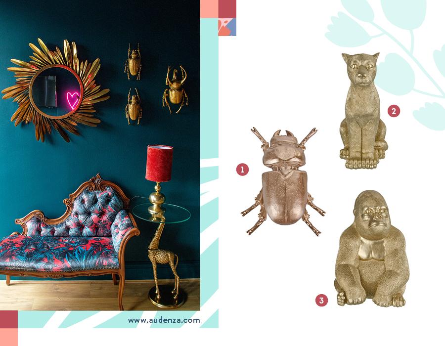 Una imagen dividida en dos partes. En la izquierda, una ambientación con una muralla azúl petróleo, en la que están colgadas tres figuras de escarabajos dorados de adorno y también un espejo del mismo color. Hay un diván estilo poltrona con un estampado llamativo, y una mesita con forma de jirafa dorada. Sobre ella, hay una lámpara dorada con pantalla roja. La imagen de la derecha son tres objetos dorados de animales, un escarabajo, un puma y un gorila.