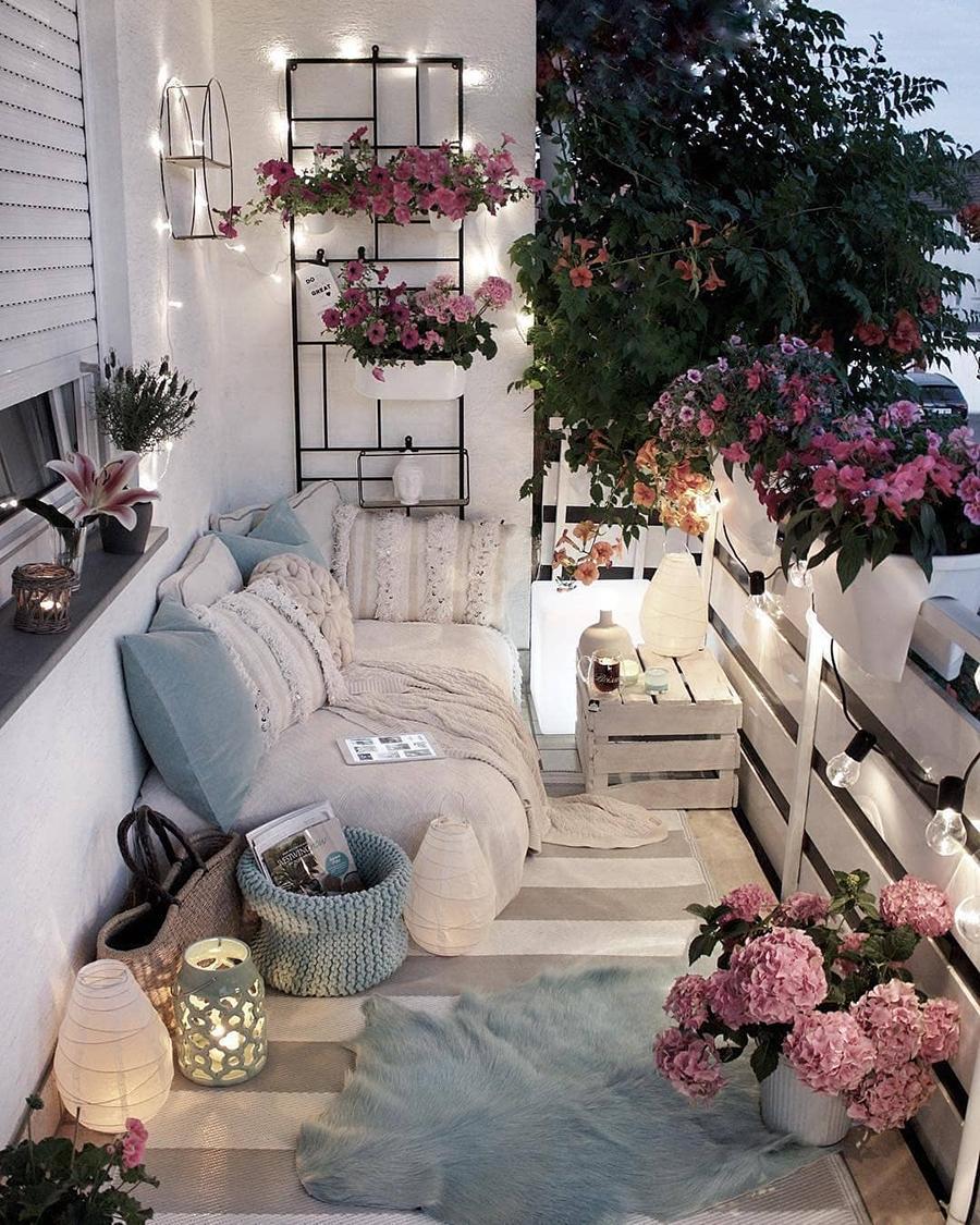 Terraza con varios textiles decorativos. Un sofá con cojines, mantas y dos alfombras.