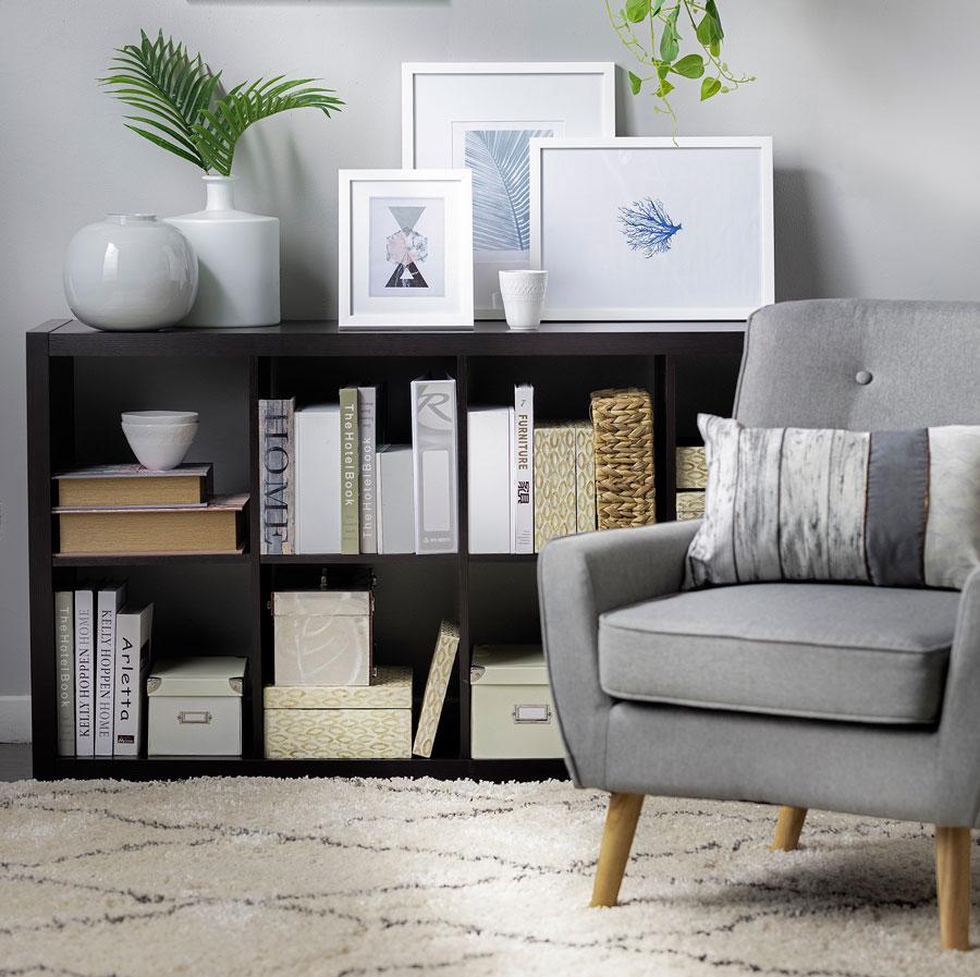 Una estantería baja en un living, con espacio para poner libros y cajas de organización. Sobre su superficie hay cuadros, floreros y adornos.
