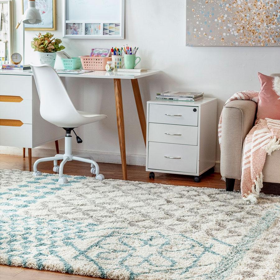 Un escritorio en el living, con un mueble con cajones y ruedas, que sirve para poner revistas arriba y como espacio de almacenamiento.