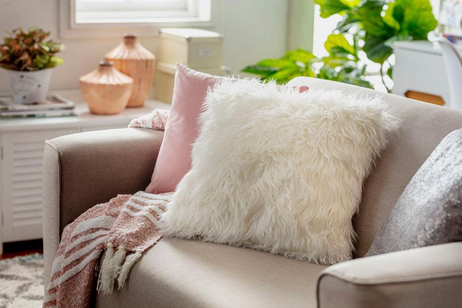 Sofá de cuero con un cojín decorativo peludo blanco
