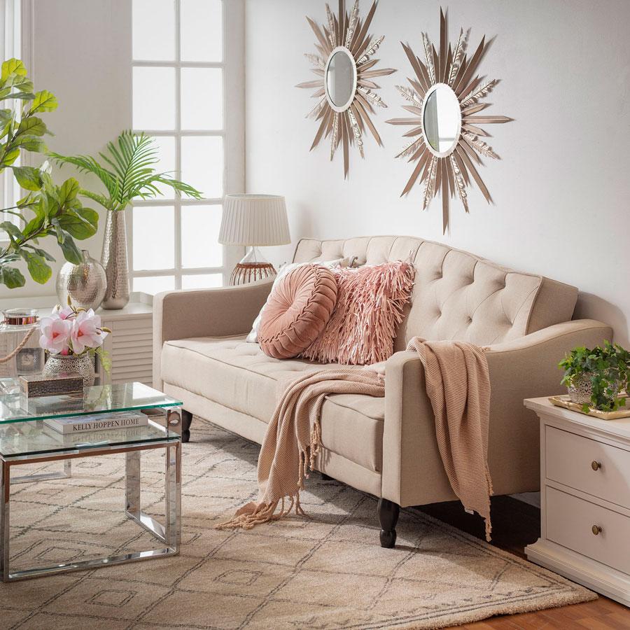 Un sofá con gran respaldo y cojines decorativos.