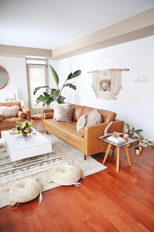 Living decorado en el estilo boho chic con paleta de colores característica del estilo. Muchas fibras naturales en la alfombra, pouf, textiles como cojines sobre el sofá y adornos de pared. Materiales como cuero en el sillón y madera, y plantas.