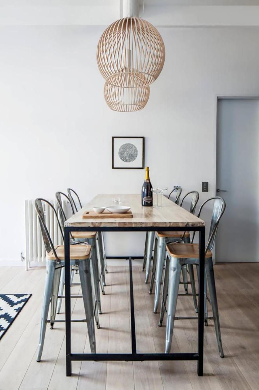 Comedor de decoración industrial con muebles de metal, paleta de colores característica del estilo, grandes espacios y lámparas colgantes.