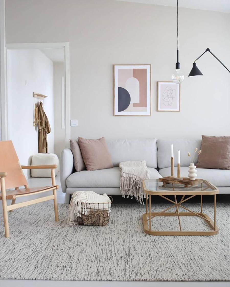 Living con decoración nórdica. Alfombra en tonos grises, paleta de colores claras. Acentos de colores en cojines decorativos, arte y silla.