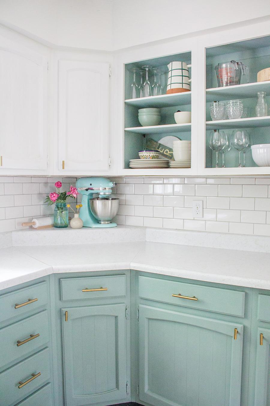 Una cocina en que el meble y el fondo de las vitrinas están pintados del mismo color turquesa pastel.