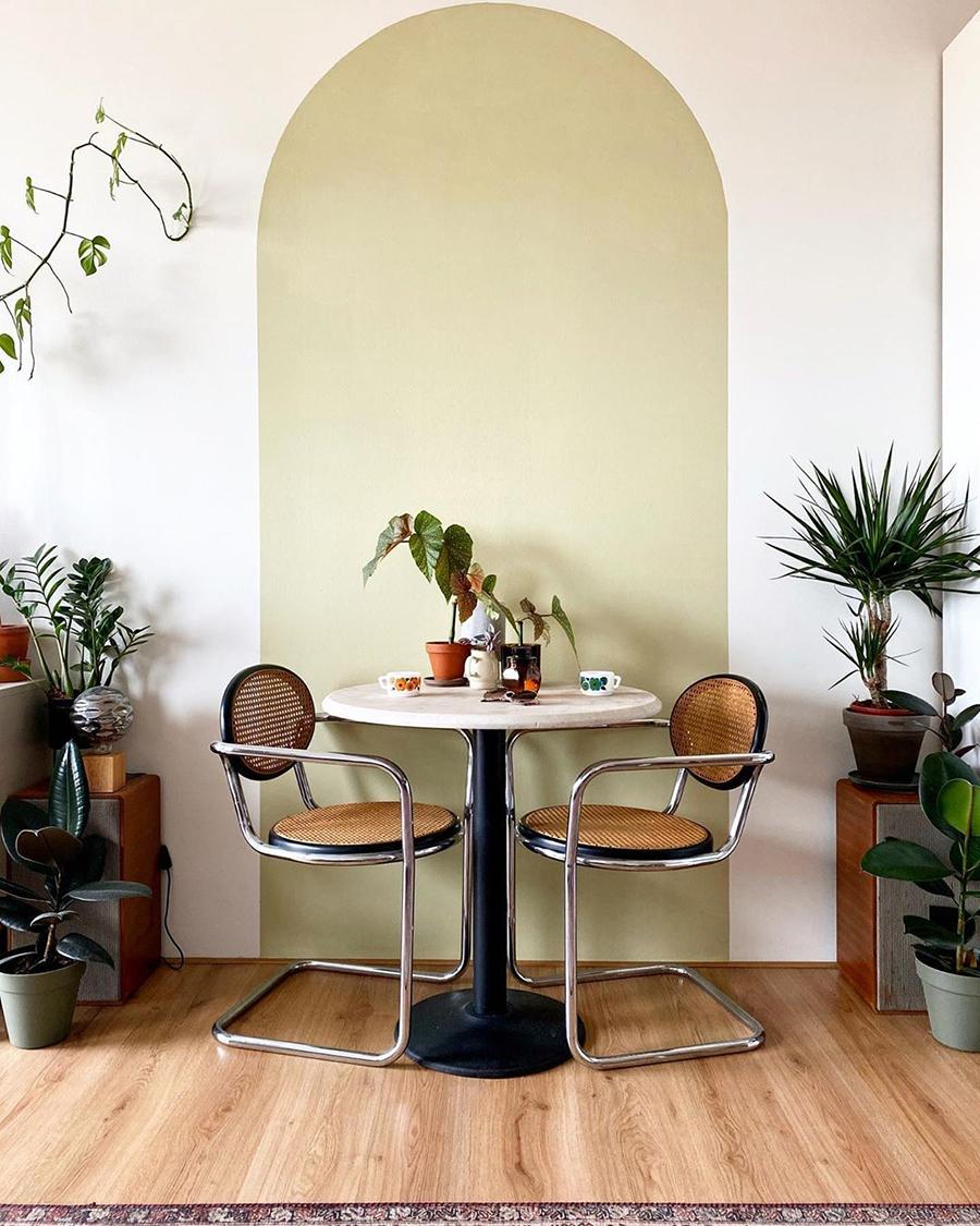 Un comedor pequeño con un arco pintado en la pared que le da mucho estilo.