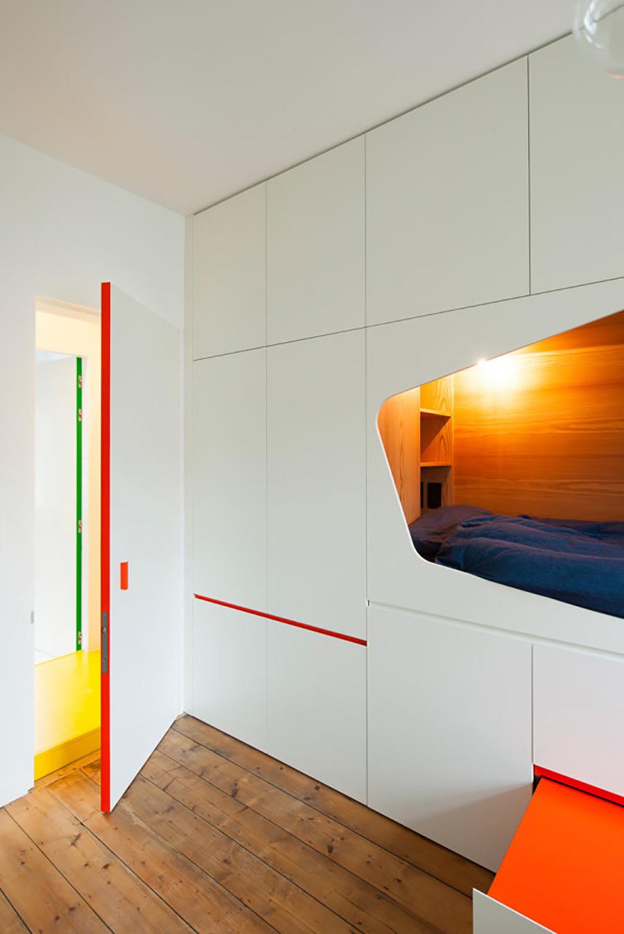 En una habitación con paredes y puerta de color blanco, el borde interior de ésta última está pintado de un color rojo brillante.