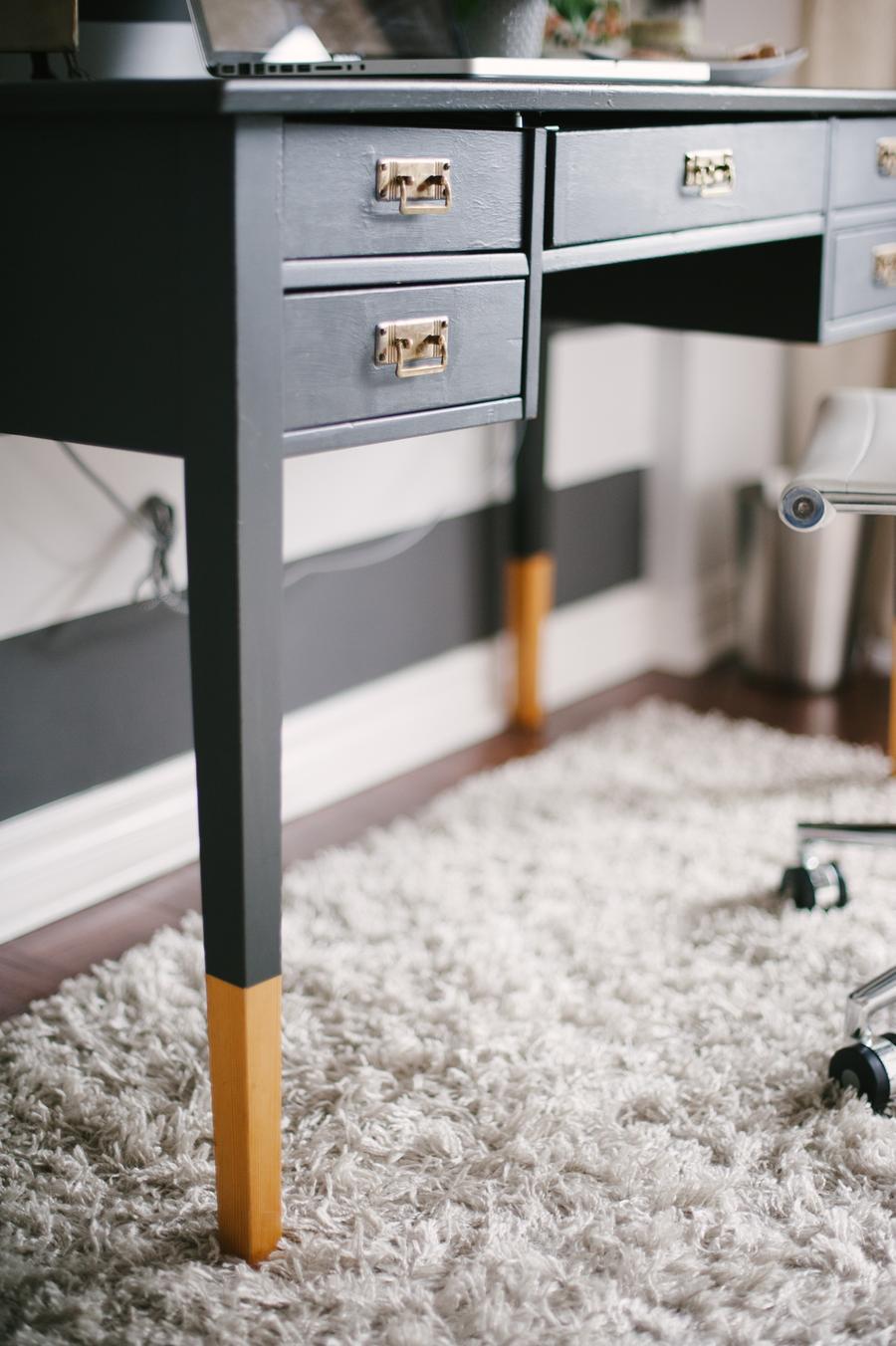 Un escritorio de color negro tiene una parte de sus patas pintadas de color mostaza.