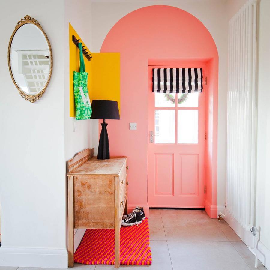 En el pasillo de la imagen hay un arco de piso a muro para ayudar a definirlo, y también un rectángulo de color amarillo vibrante para poner percheros.