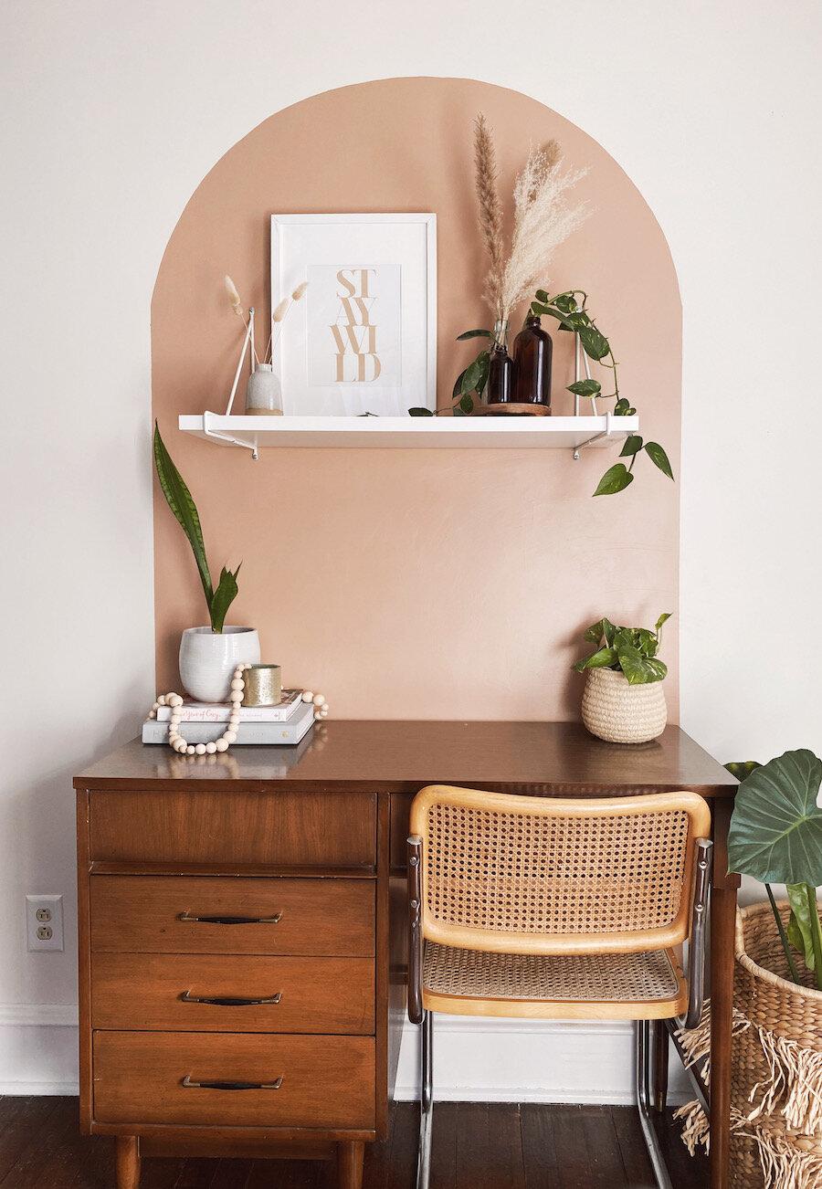 Un escritorio delimitado por un arco de color pintado a la pared.