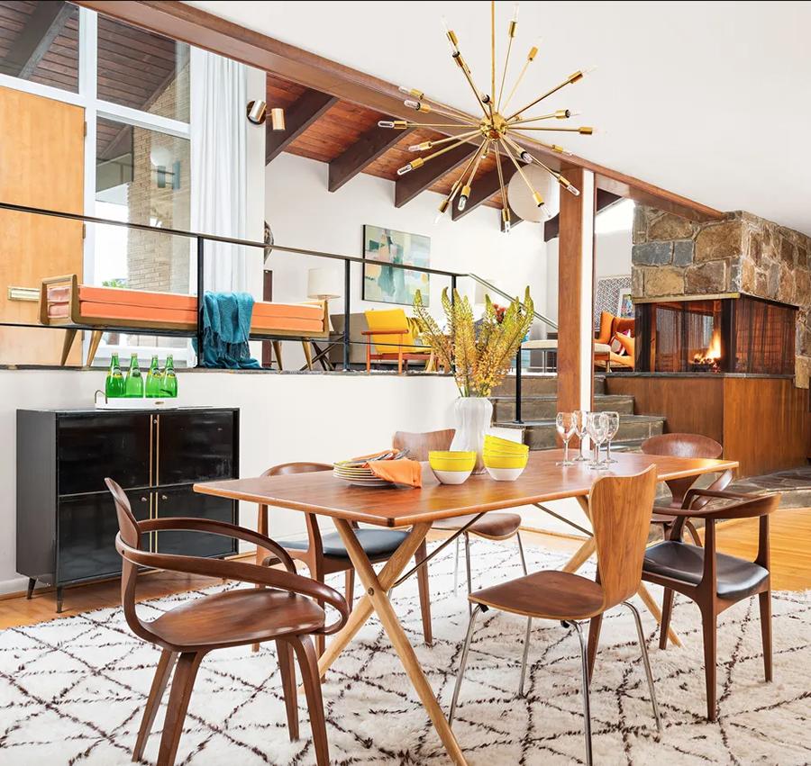 Un comedor decorado al estilo vintage moderno. Destaca el uso de la madera y la lámpara colgante.