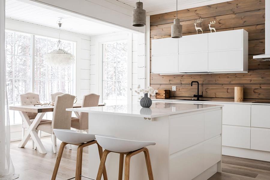 Asiento estilo nórdico para isla de cocina, de color blanco con patas de madera color claro. Tienen respaldo bajo.