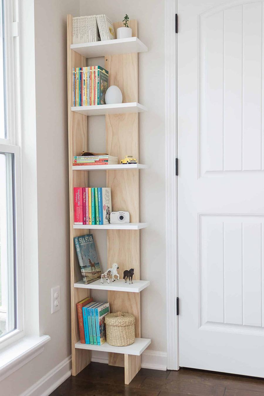 Una estantería de madera para poner en la esquina, con borde por un lado, para que los libros que se encuentran sobre ella en la fotografía tengan tope y no se caigan.