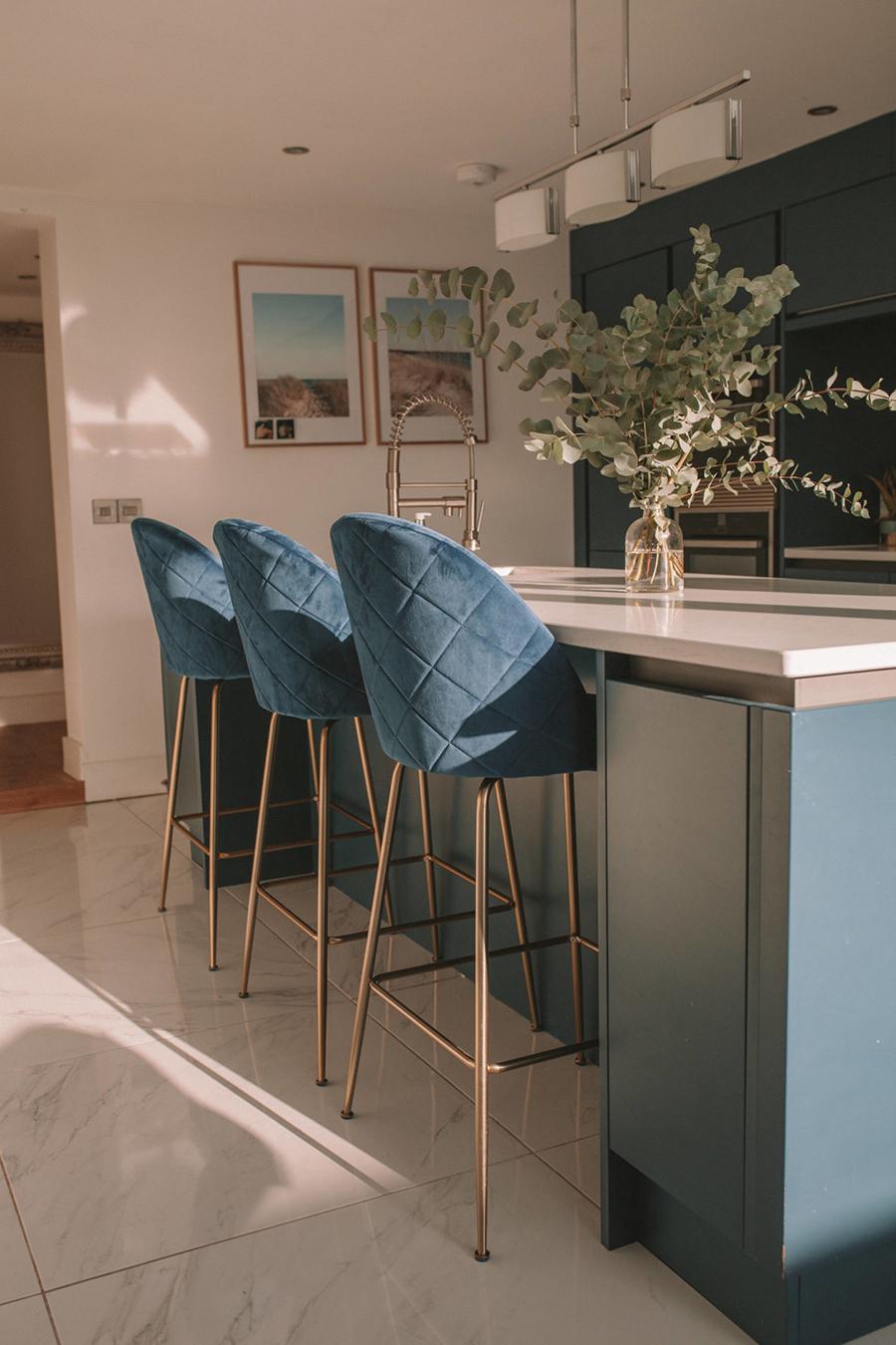 Asientos para isla de cocina de estilo glam, de terciopelo color azul petróleo y patas metálicas cobrizo, con respaldo alto.