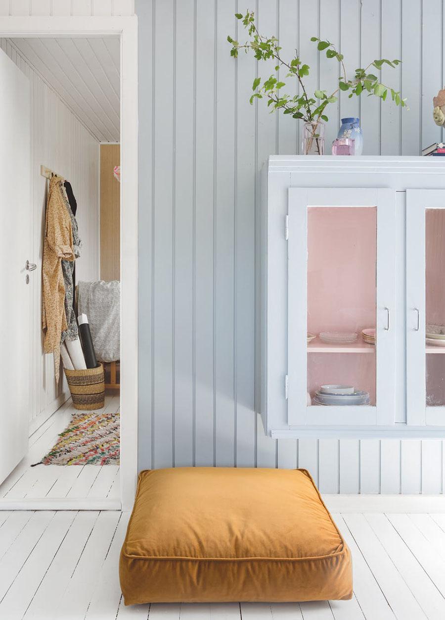 En una vitrina para poner vajilla, la pared del fondo es de color rosado, que combina con el menaje.
