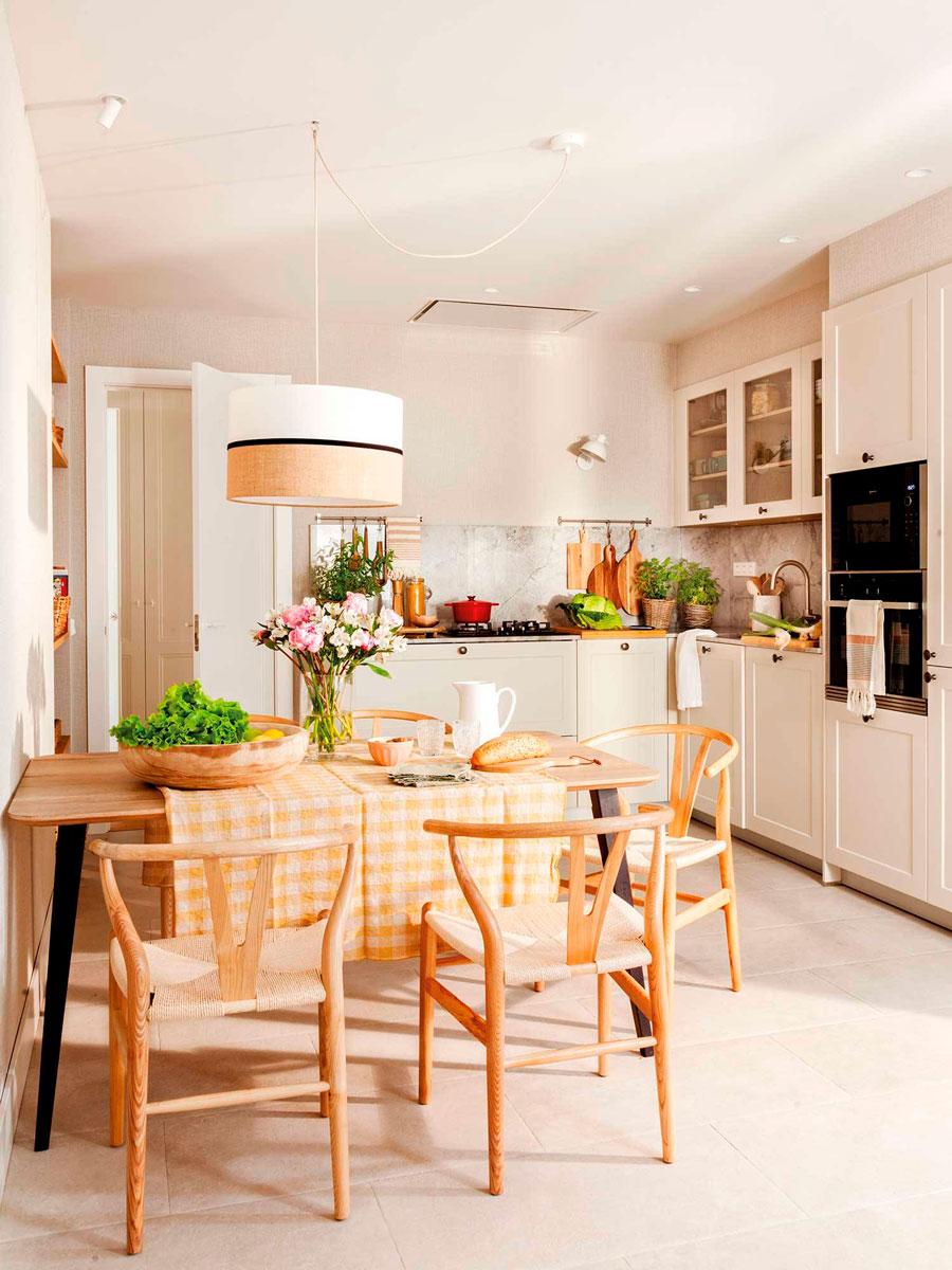 Una cocina con distintos puntos de iluminación: una lámpara colgante de techo y focos empotrados.