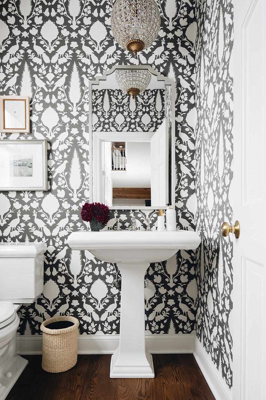 Un baño con un papel mural con un diseño muy original en blanco y negro.