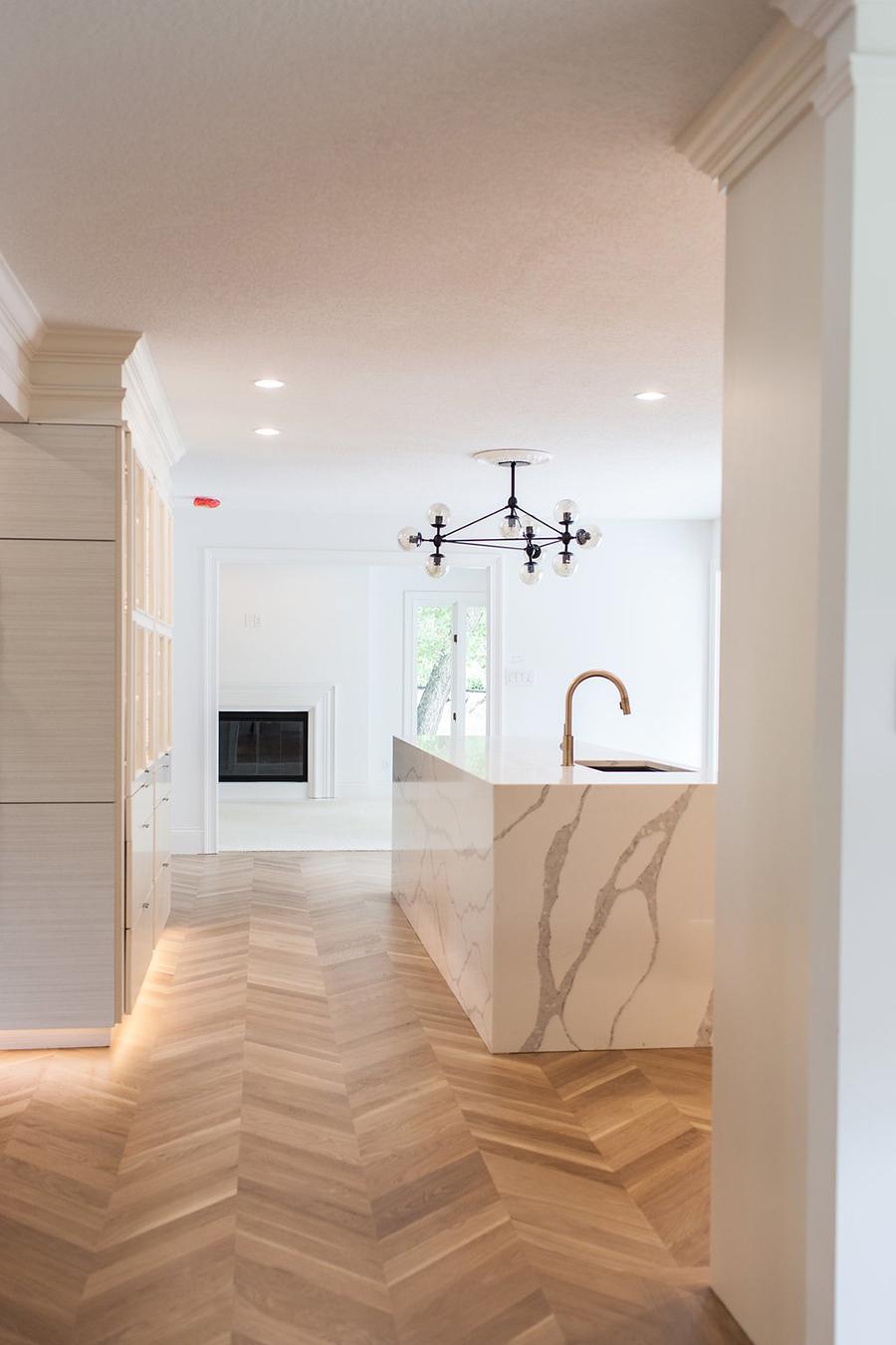 En esta cocina hay varios puntos de iluminación, bajo los muebles, en el techo y una gran lámpara decorativa.