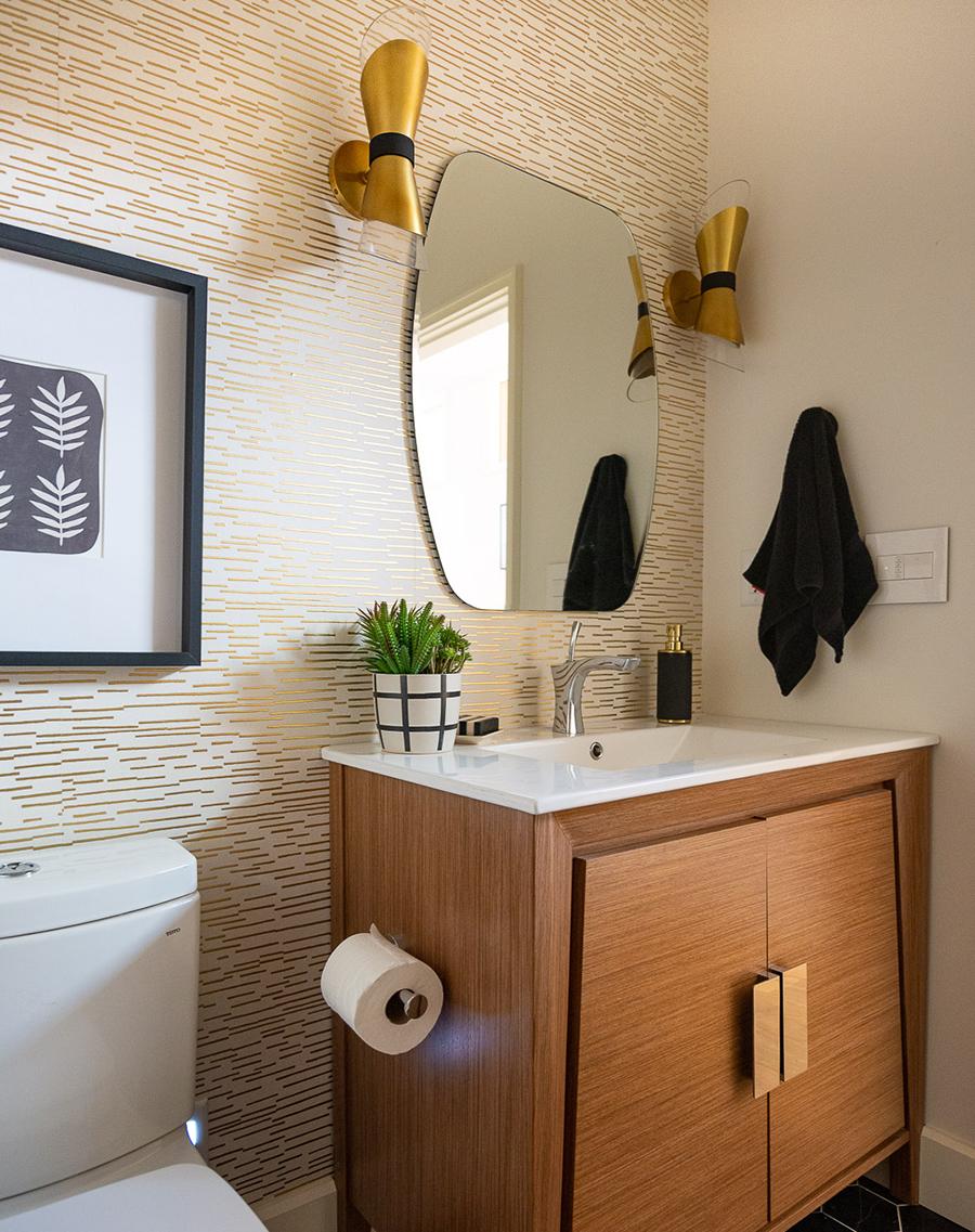 """Un papel mural con líneas irregulares doradas otorga un estilo """"vintage moderno"""" al baño."""