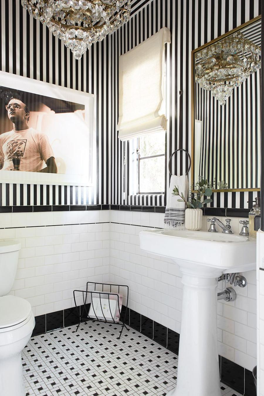 Un papel mural con base blanca y líneas gruesas y verticales de color negro pueden darle a un baño un estilo glam.