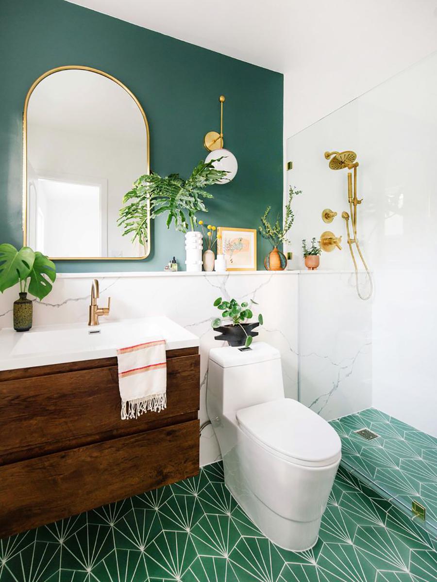 Un baño decorado con estilo vintage moderno, con toques dorado y plantas que combinan con el muro y piso verde.
