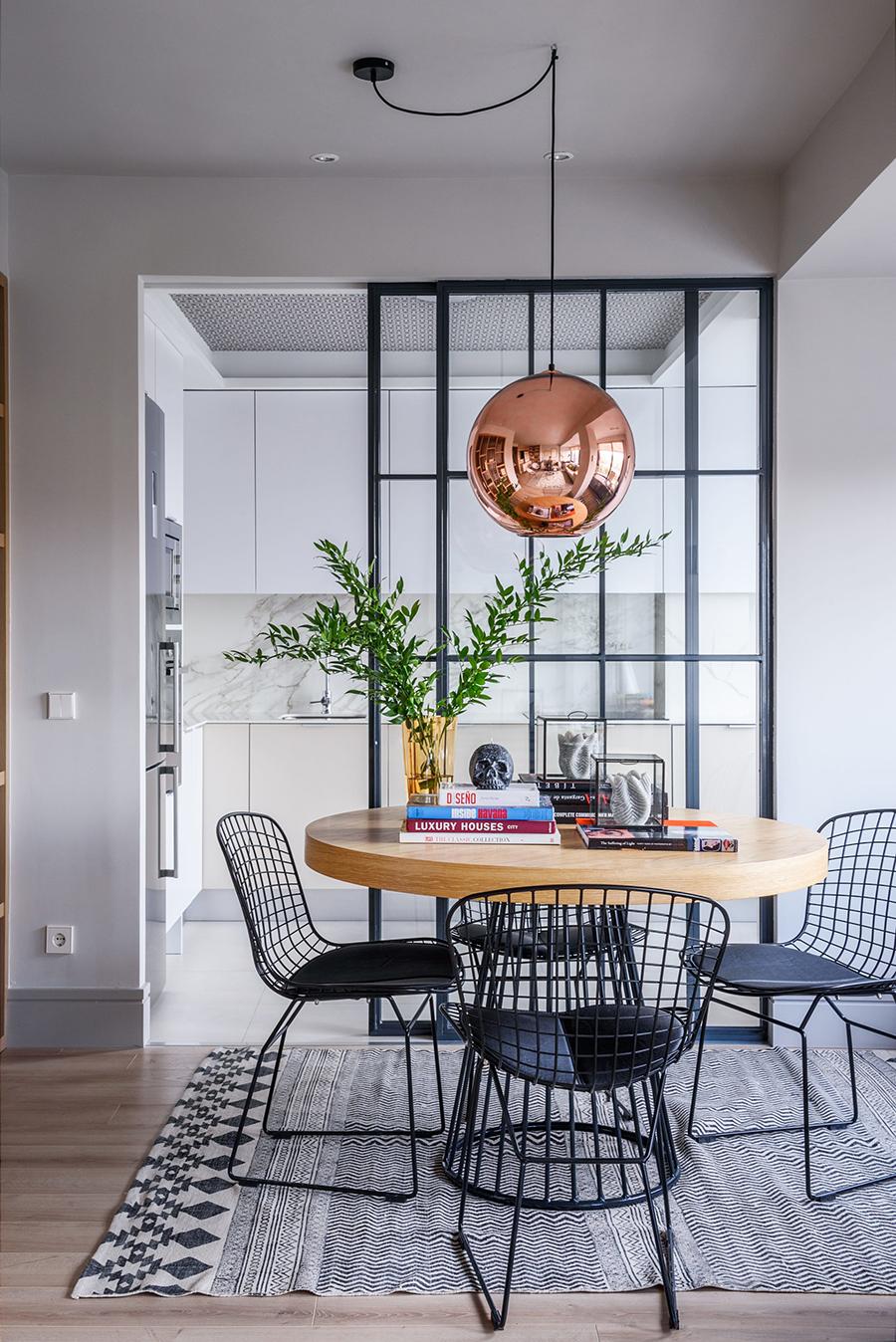 La imagen muestra a una cocina separada del comedor por una puerta de vidrio.