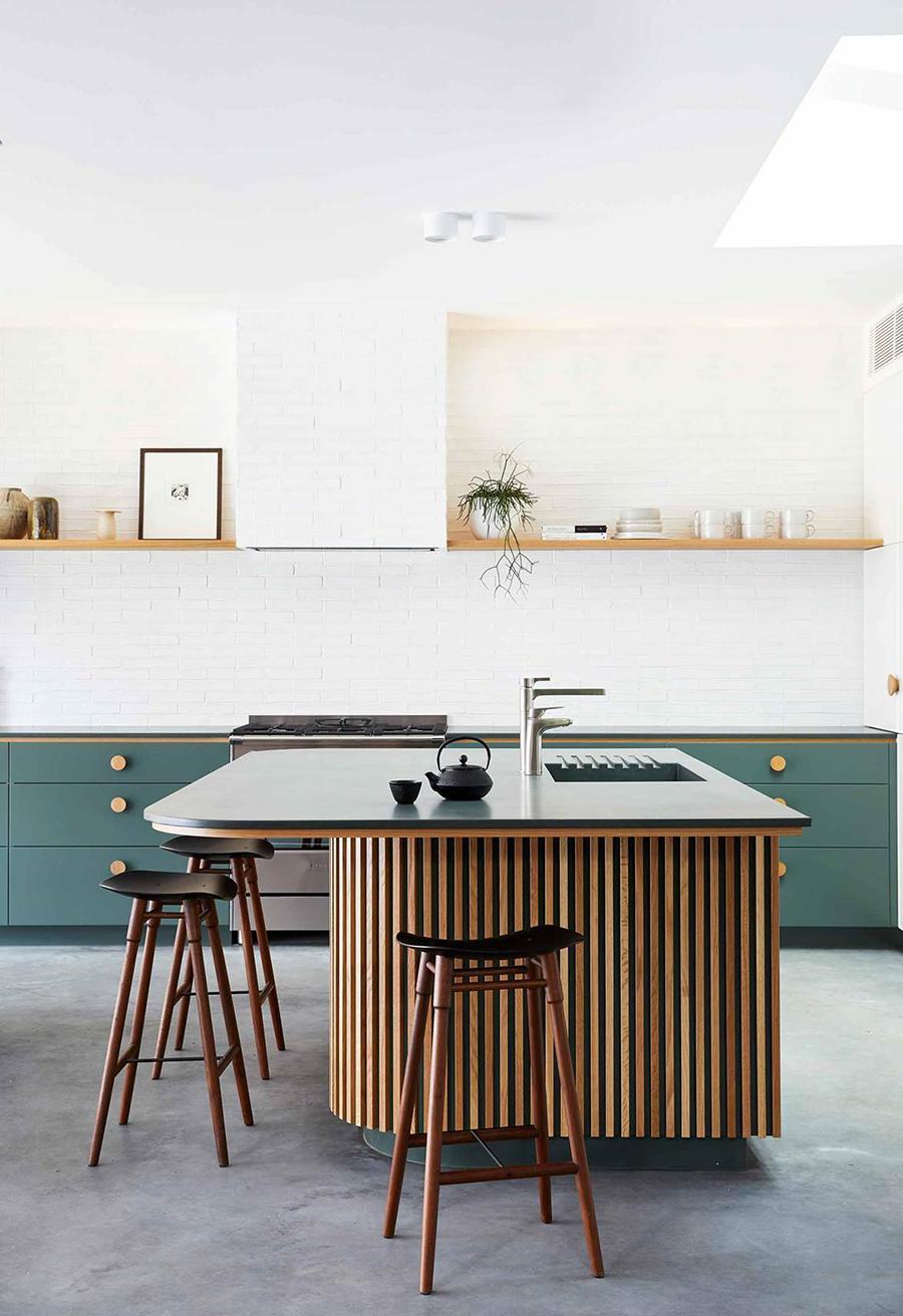 En la imagen se muestra a una cocina tipo isla, con una decoración con colores suaves y materiales naturales, como la madera.