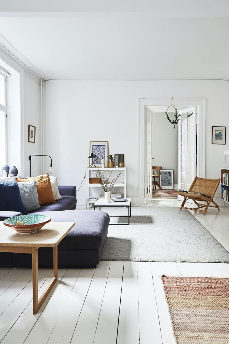 Un living con piso de madera y alfombra.
