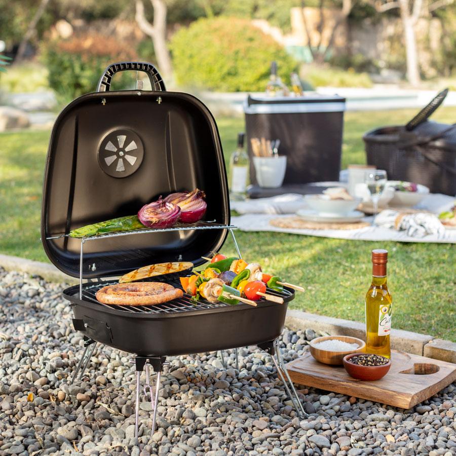 En la imagen se muestra una parrilla portátil en un picnic, haciendo un asado.