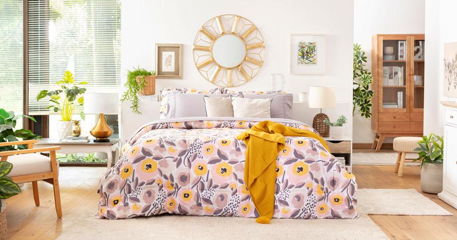 En la imagen se muestra un dormitorio con una cama grande, ubicada a centro de la pieza. La cama está cubierta por un plumón floreado en todos amarillos y lilas.