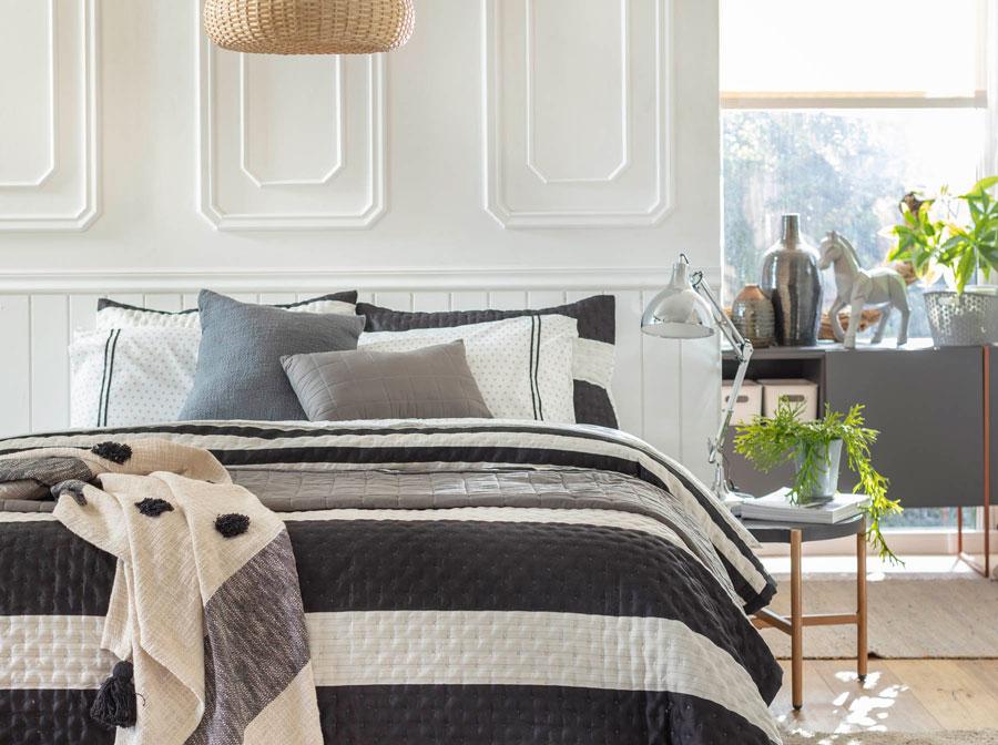 En esta imagen se muestra una cama de tamaño grande, con un cobertor con rayas blancas y negras y cojines en tonos azules y grises.