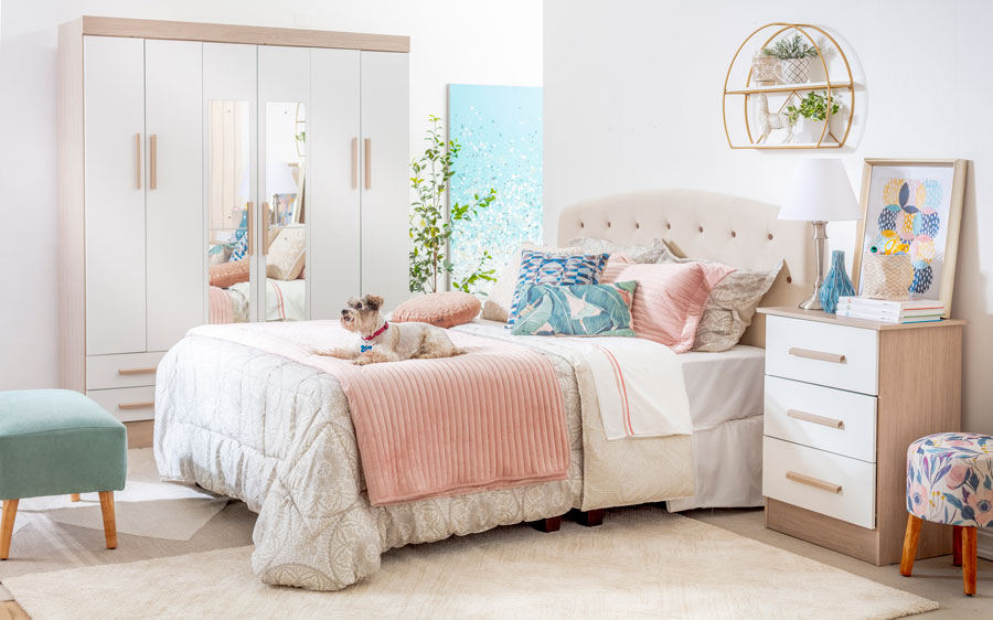 En la imagen se ve una cama ubicada al lado de un closet de puertas abatibles. La cama está decorada en todos cremas, rosados y celestes.
