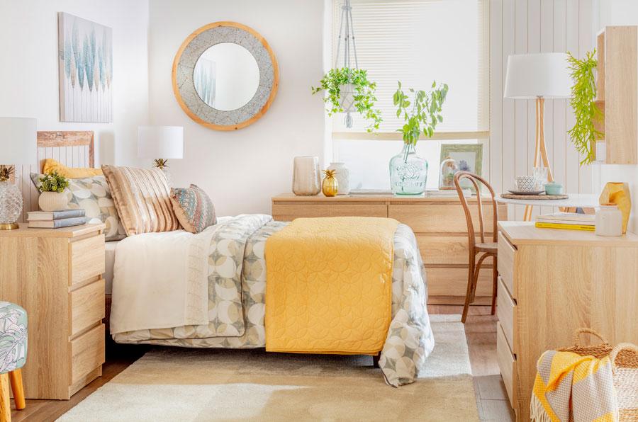 Esta imagen muestra una pieza mediana con una cama en la esquina. La cama está cubierta con un plumón en todos amarillos y plomos. También tiene una piecera de color amarilla.