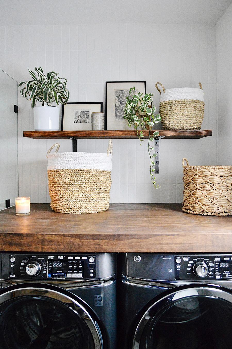 En la imagen se muestran dos lavadora bajo una cubierta de madera con cestos para organizar la ropa.