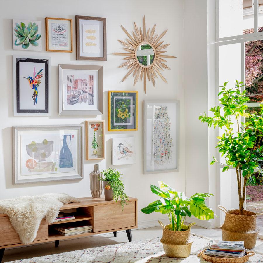 """Varios cuadros y marcos de fotos colgados en la pared, formando una especie de """"galería de arte""""."""