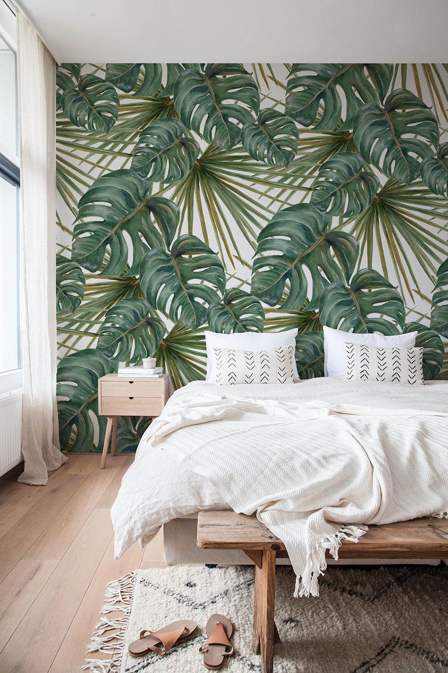 Un dormitorio con una pared decorada con papel mural de grandes hojas, estilo tropical.
