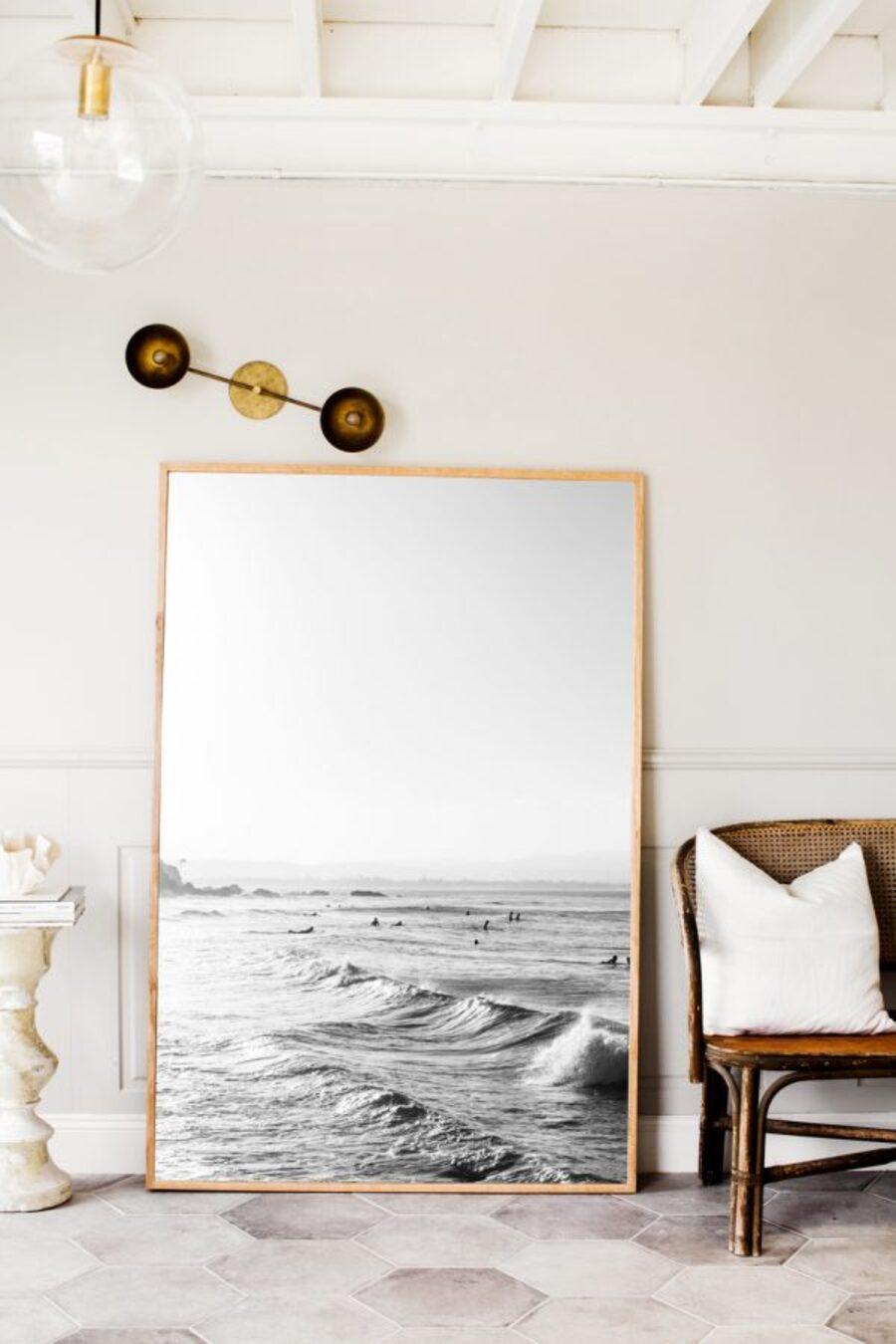 Un gran cuadro de un paisaje marino apoyado en la pared.