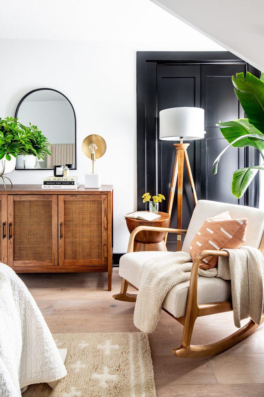 Un rincón dedicado al relajo con una poltrona mecedora, una lámpara de pie y plantas.